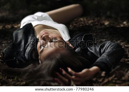 Beautiful young woman lying on the grass