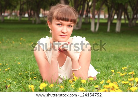 beautiful young woman lying on the grass in the park, good emotions