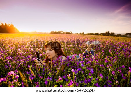 Beautiful young woman lying on the nature and talking at cellphone