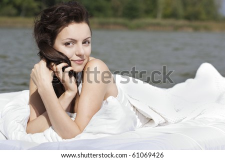 Beautiful young woman lying on the white bed in the sea