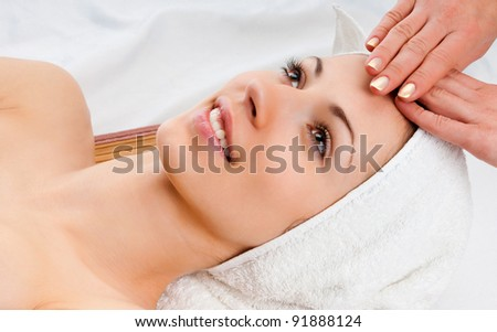 beautiful young woman lying relaxed in a spa salon and receiving facial massage