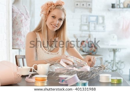 Beautiful young woman making decoration in retro style.