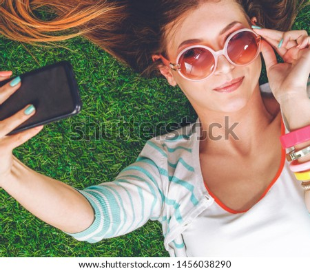 Beautiful young woman making selfie by her phone while lying in green grass. Beautiful young woman making selfie