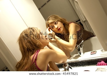 Beautiful Young Woman Making Up with Eyeshadow in front of the Dresser