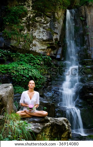 Beautiful young woman meditating and showing a lotus flower while doing yoga in the nature near waterfall - stock photo