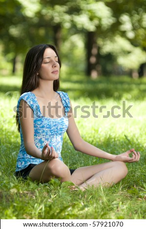 Beautiful young woman meditating in lotus position while doing yoga in the nature