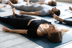 Beautiful young woman meditating in Savasana pose on floor close up, practicing yoga at group lesson, doing Corpse exercise on mats, training, working out in modern yoga studio, center