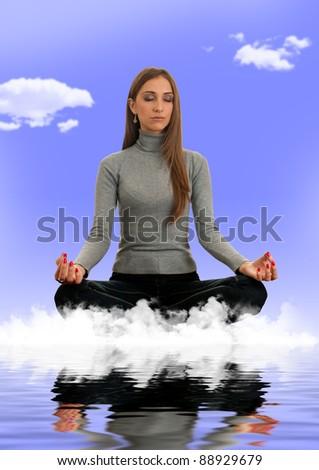 Beautiful young woman meditating on a cloud