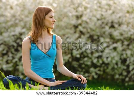 Beautiful young woman meditating outdoors