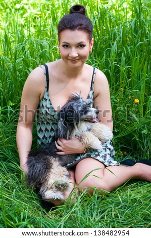 Beautiful young woman model sitting together on fresh green grass with her pet young Chinese crested dog, smiling happily, looking at camera. Against nature green background