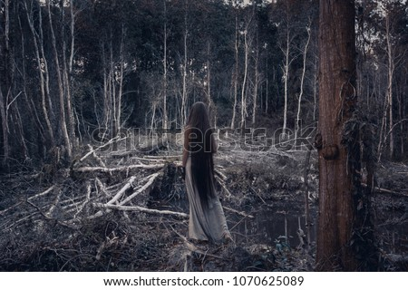 Beautiful young woman model with very long hair in forest. witch craft concept #1070625089