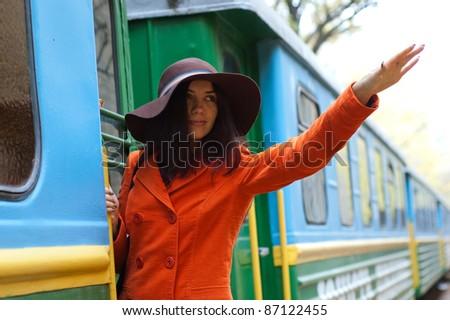 beautiful young woman near a train