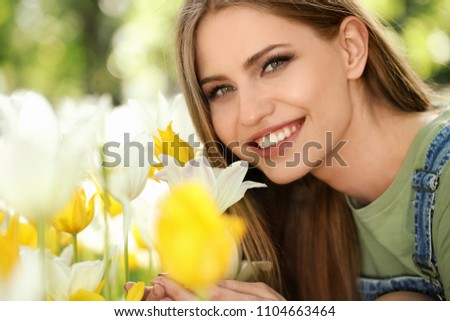 Beautiful young woman near blossoming tulips in green park on sunny spring day #1104663464