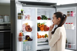 Beautiful young woman near open refrigerator in kitchen