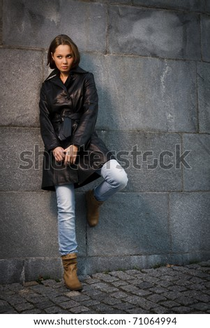 Beautiful young woman near stone wall - stock photo