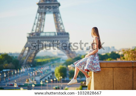 Beautiful young woman near the Eiffel tower in Paris, France