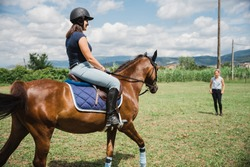 Beautiful young woman on a summer day rides with his horse and takes lessons from an experienced riding teacher - Millennial has fun with his animal friend