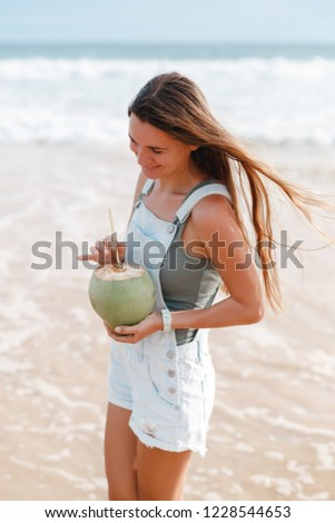 Beautiful young woman  on a tropical beach enjoying ocean sea view, taking deep breath and dink cold fresh coconut