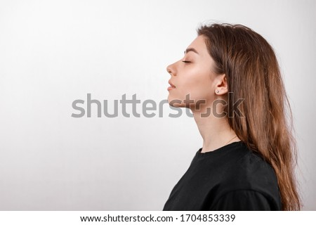 beautiful young woman on a white background stands in profile in a black shirt. copyspace. isolate Сток-фото ©