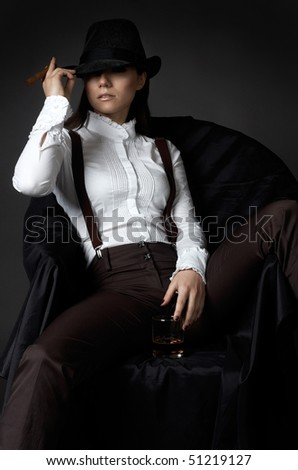 beautiful young woman on an armchair in hat smoking cigare - stock photo