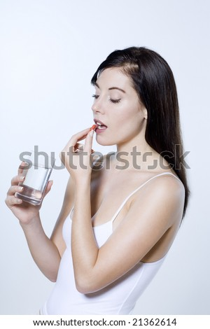 beautiful young woman on isolated background eating yogourt