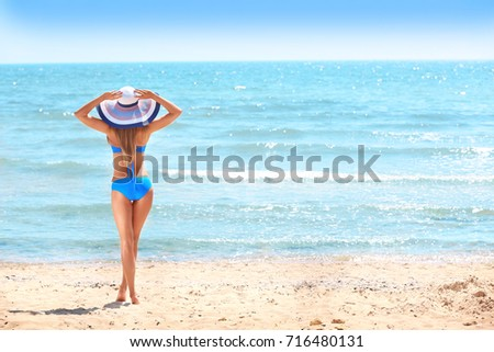 Beautiful young woman on sea beach #716480131