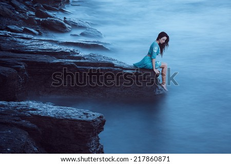 Beautiful young woman on sea in twilight. Long time exposure