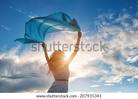 Beautiful young woman on sunset background with blue tissue.