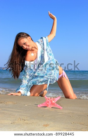 Beautiful young woman on the beach with a star fish - Selective focus