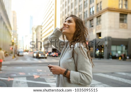 Beautiful young woman on the boulevard in urban scenery, downtown, at sunset, holding smartphone and looking side.