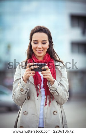 Beautiful young woman on the street text messaging.