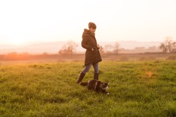 Beautiful young woman on walk with her Norwegian Forest cat in meadow at sunset. Soft light.