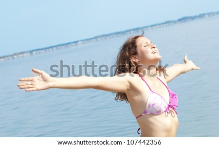 beautiful young woman opened her hands with delight at the blue sky - Girl embraces the whole world