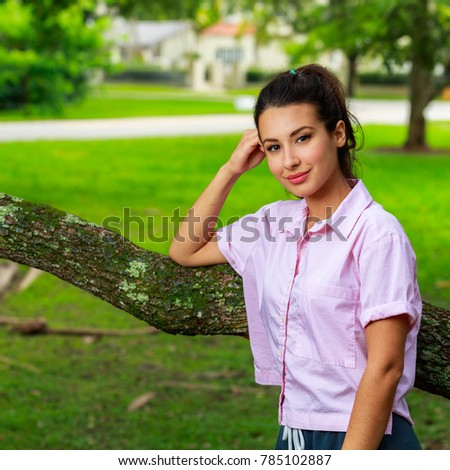 Beautiful young woman outdoor portrait in a park setting.