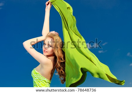 Beautiful young woman outdoors over blue sky.