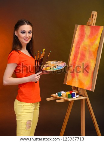beautiful young woman painter at work, on bright color background