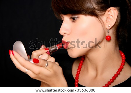 stock photo Beautiful young woman painting lips in red color
