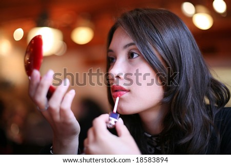 Beautiful young woman painting lips in red color. Shallow DOF.