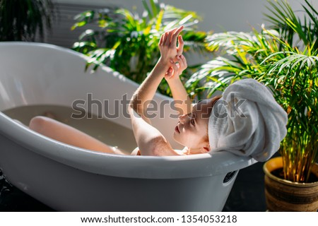 Beautiful young woman pampering her body in water, taking bath with mineral oils in relaxing atmosphere of hotel spa zone at sunny morning Сток-фото ©
