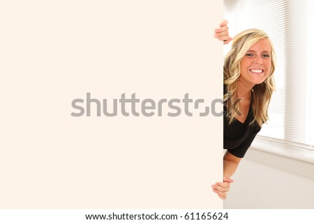 Beautiful young woman peeking out behind wall of office or school building.