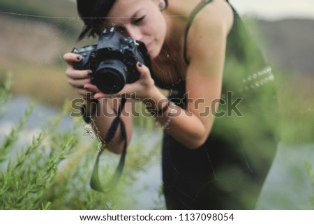 Beautiful young woman photographer wearing black clothes taking macro photos of nature and insects outdoors. Tiger spider in its spider web being photographed by a young photographer in countryside.