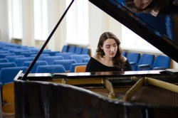 Beautiful young woman playing and singing on grand piano alone in concert hall during daytime