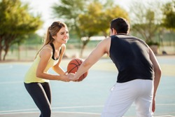 Beautiful young woman playing basketball with her boyfriend on a court outdoors and having some fun