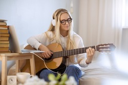 Beautiful young woman playing guitar while sitting on bed at home. Portrait of cute girl in casual clothes wearing glasses headphones at guitar practice at home.