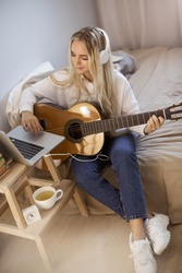 Beautiful young woman playing guitar while sitting on bed at home. Portrait of cute girl in casual clothes wearing headphones at guitar practice at home.