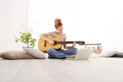Beautiful young woman playing guitar with computer, learn to play with an online course, sitting on the floor in casual clothes at home