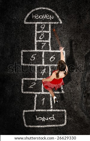 Beautiful young woman playing hopscotch with a red dress