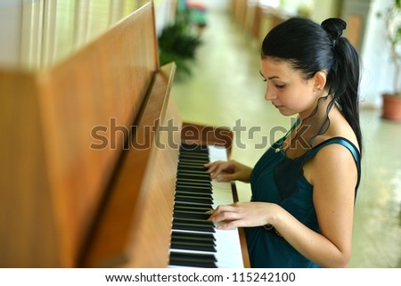 beautiful young woman playing the piano