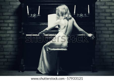 beautiful young woman playing the piano (black and white photo) #57933121