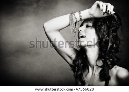 beautiful young woman playing with bracelet, bw, studio shot